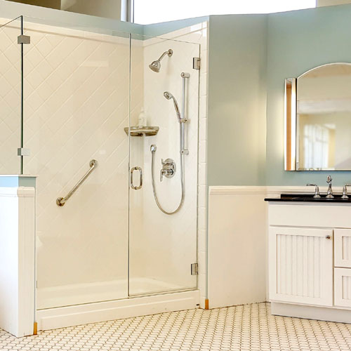 all glass shower enclosure with pastel bathroom